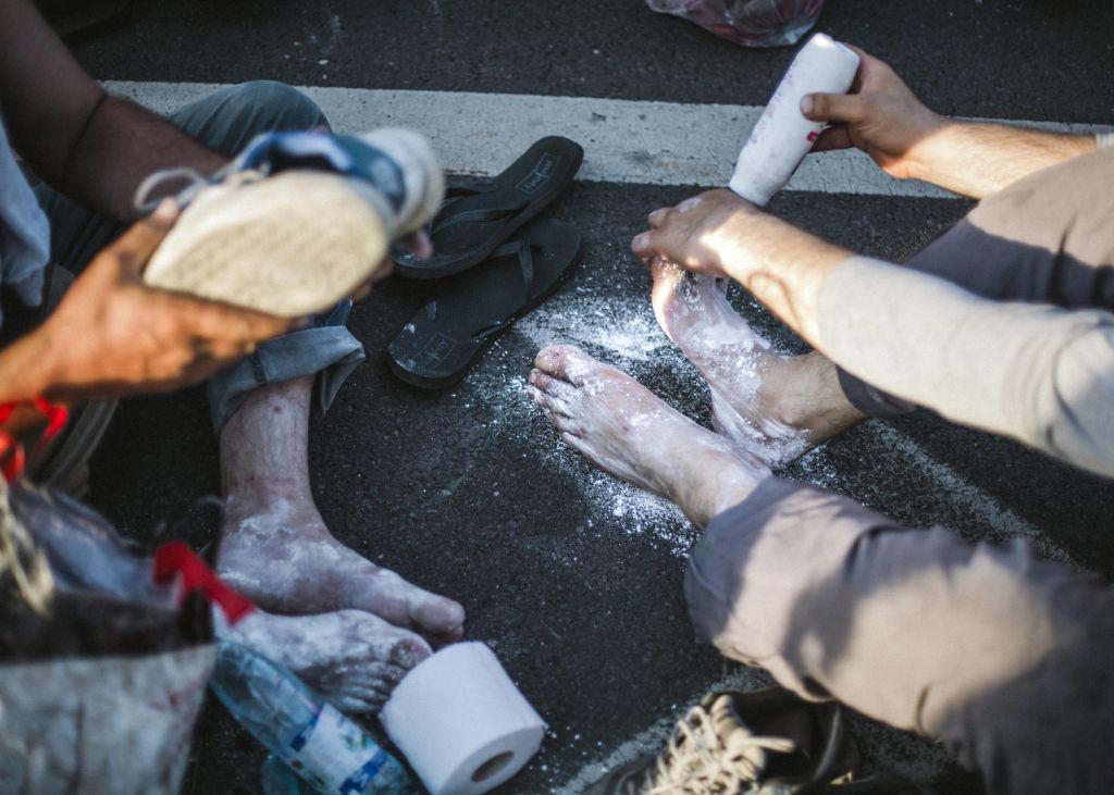 A menetelésben kidörzsölődött lábukat púderezik a menekültes az M1-es autópálya mellett.