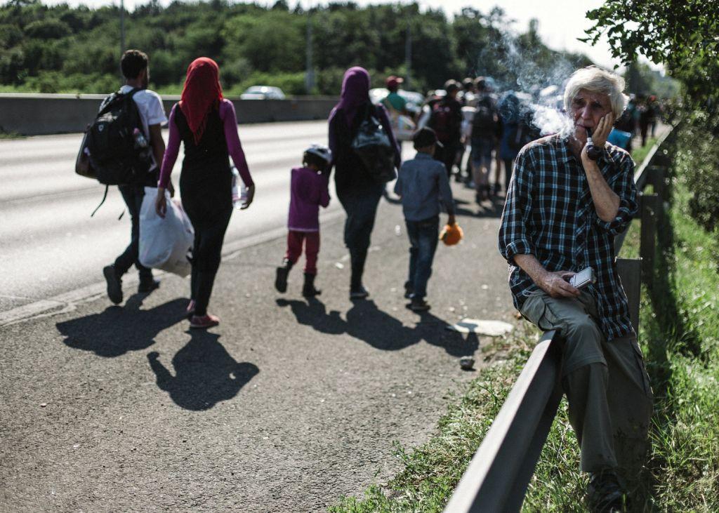 Meghatódott magyar férfi nézi az M1-en gyalogló menekülteket.