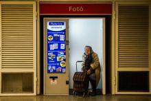 A képre várva Egy idős asszony üldögél egy igazolvány automatában a budapesti Blaha Lujza tér aluljárójában 2015. május 9-én.