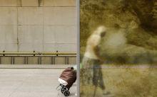 Átviszi Utas gurítja el a táskáját egy átlátszó fal előtt a Móricz Zsigmond körtér metróállomásnál. A négyes metrót több mint egy éve használhatják az utasok.