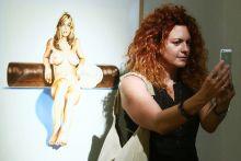 Szelfi A kaliforniai művész, Mel Ramos kiállítása alatt ihletett kapott hölgy szelfizik Ramos egyik műve előtt a szegedi Reök palotában. 2015.