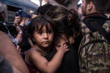 Anyu karjaiban A rendőrség lezárta és kitereli a Keleti pályaudvarról a Németországba tartó vonatokra várakozó menekülteket 2015. szeptember 1-jén Budapesten. Egy kislány anyukája karjaiban keresi a biztonságot.