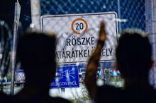 """A röszkei menedékkérők egy csoportja 2015. szeptember 16. menekültek, avagy migránsok csoportja a röszkei zavargást követő órákban, a szögesdrótok előtt továbbra is a határnyitást követelték. """"A menekültek fegyveres konfliktus vagy üldöztetés miatt hagyják el a hazájukat, velük ellentétben a migránsok egy jobb élet reményében érkeznek egy új országba."""""""