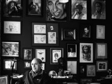"""""""Önimádó Fal"""" Kárpáti Tamás, író, főszerkesztő, műgyűjtő.  Lakásának """"önimádó falát"""" róla készült portrék díszítik. Többek között Gyémánt László, Müller Árpád, Tandori Dezső, Darvas Iván alkotásai a háttérben."""