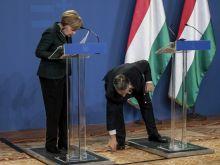 Meghajlás Orbán Viktor miniszterelnök felveszi vendége, a Budapesten tartózkodó Angela Merkel német kancellár leejtett tollát a megbeszélésük után tartott sajtótájékoztatón a Parlamentben 2015. február 2-án.
