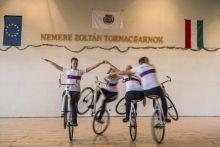 Művészi teremkerékpár A művészi kerékpár szakágban a sportolók versenyezhetnek, hogy ki tud szebb és nehezebb elemeket bemutatni. Egy kicsit hasonlít a műkorcsolyára és a tornára, akrobatikus elemeket tartalmaz, a versenyzőktől egyensúlyérzéket, koncentrációt és bátorságot kíván. Különleges örökhajtású kerékpárokat használnak, a meghajtó és a meghajtott lánckerék közötti 1:1 arányú áttétellel. A kormány is speciális, a versenyzők állnak ill. ülnek is rajta. A kerékpárokat visszafelé is könnyű hajtani. Képriport a 2015 szeptember 26.án Bokodon rendezett Teremkerékpáros kupáról.