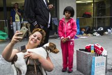 Cím nélkül 2015.09.05., Budapest, Baross tér. Pesti járókelő szelfizik kutyája és egy menekült kislány társaságában.
