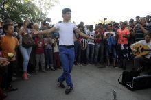Menekültek a Nyugatinál Budapest, 2015. 09. 04. Táncoló afgán fiú a Nyugati pályaudvar mögötti menekült állomáson, ahol a segítők zenei műsort is szerveztek.