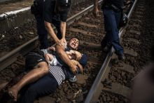 x A Syrian man holds on to his wife's, as Hungarian riot police attempt to take them to a refugee camp. The man had pulled his family down to the ground at Bicske railway station after authorities had