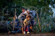 Irány az erdő! Augusztus 27-én hajnalban egy menekült család próbál átjutni a szögesdrót alatt Magyarországra, Röszke közelében.