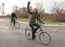 Kétkeréken Colleen Bell amerikai nagykövet kerékpározás közben integet a Balf és Fertőrákos közötti új kerékpárúton  amit előtte adták át a mögötte kerékpározó Fazekas Sándor földművelésügyi miniszterrel.