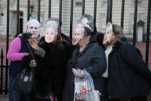 Selfie a Buckingham Palota előtt! Néhány főből álló csoport selfie-t készít álarcban a Buckingham Palota előtt.