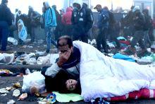 Ébredés Európában 2015.09.23. Röszke magyar-szerb határ Éjjel érkezett menekültek az éjszakát szabadban töltötték, Ébredő szír apuka fiával.