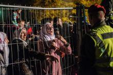 Anyai ösztön Menekültek kiabálnak a határőröknek az osztrák-szlovén határon Sentiljnél 2015. október 28-án. A gyerekeiket kiemelték a tömegből, szétszakítva az órák óta a kerítés tövében várakozó családot.