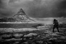 Kirkjufell Fotós dacol az orkán erejű széllel és esővel az észak izlandi jellegzetes, boszorkánysüveget formázó Kirkjufell hegy előterében.