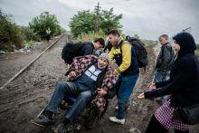 Hátrafelé Európába Mozgássérült szíriai menekült férfit tol be családja Magyarországra, mielőtt még lezárták volna a határt Röszkénél.