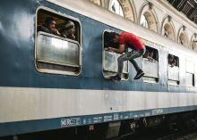Mindenáron Menekült férfi mászik be egy vonat ablakán a Keleti pályaudvaron.