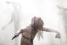Hőség Sziget Fesztiválon a Nagyszínpad előtt felkavart port tűzoltó slaggal nyomják le, amit a fesztiválozók is szeretnek kihasználni a felüdülésre. Budapest, 2015.08.14