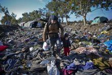 Úton Menekült férfi kel át gyermekével a szerb-horvát határon Berkasovónál, a hátrahagyott, takarókon.