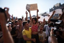 - A migrant holds up a migrant girl who holds up signs at the Keleti railway station in Budapest, Hungary on 1 September 2015 protesting the Hungarian authorities' closure of trains to Germany.