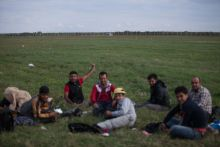 - A group of migrants merrily point at the police guarding Hungary's newly built fence after crossing on the railroad tracks on 8 September 2015 near Roszke