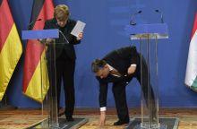Segítő kéz Orbán Viktor miniszterelnök felveszi Angela Merkel német kancellár leejtett tollát a megbeszélésük után tartott sajtótájékoztatón a Parlamentben 2015. február 2-án.