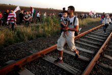 Jobbikos felvonulás a határon Határzárat hirdetett és zöldhatárhoz vonult a Jobbik szeptember 2-án. Egy gyermekét cipelő migráns figyelő a magyar zászlóval vonulókat.