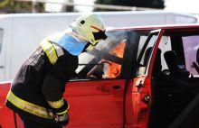 """Lángoló autó A pécsi tűzoltók egy gyakorlat során autót gyújtottak fel, majd oltották el egy valós szituációt gyakorolva ezzel. A végén a kilátogató kisgyermekek is kipróbálhatták milyen érzés a sugárcsővel """"locsolni""""."""