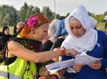 Kultúrák találkozása Horgos 2 határátkelő szeptember 16. Egy tarka ruhás svéd nő szórólapot mutat a sorban álló arab lánynak a menekültkérelem lehetőségeiről. Közben a férfi migránsok a határzárat ostromolják.