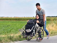 Két keréken Európába Magyarkanizsánál egy migránscsoporttól lemaradva fiatal férfi sérült tolókocsiban édesanyját két keréken maga előtt tolva szapora léptekkel igyekszik a még 10 km-re lévő EU határ felé.