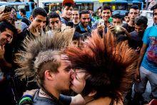 Szeress, ne háborúzz! Szerelem a káosz közepén. Menekültek előtt csókolózik két punk a Keleti pályaudvarnál. Üzenetük: Szeress, ne háborúzz! Mert a szeretet a legerősebb fegyver az erőszak ellen.