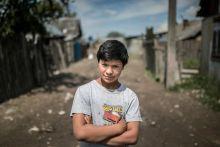 Félúton Serdülő cigány fiú portréja a a Beregszászhoz közeli romatelepen 2015. május 15-én. A telep nyomorúságos körülményei közt már az egészen fiatal fiúknak is felnőtt szerep jut.