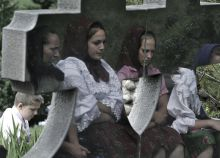 Temetésen Máramarosi nők tükröződnek egy gránit sírkövön. A fényképet észak-Romániában egy hagyományos máramarosi temetésen készítettem