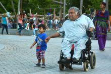 Nagypapa A büszke nagypapa önjáró tolókocsiban ülve kézen fogva vezetgeti unokáját az egyik londoni park sétaútján.