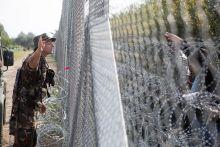 Jelbeszéd Egy honvéd elzavarja a menekültek egy csoportját a kerítéstől, a határzár első napján Röszkén.