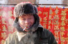 """Derű Újévi díszek árusa egy vidéki kínai piacon """"US Army"""" feliratú kabátban."""